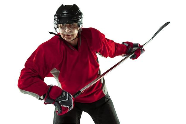 Jugador de hockey masculino con el palo en la cancha de hielo y fondo blanco.