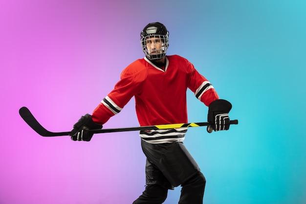 Jugador de hockey masculino con el palo en la cancha de hielo y fondo degradado de color neón