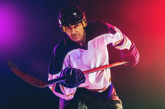 Jugador de hockey masculino con el palo en la cancha de hielo y la pared de color neón oscuro