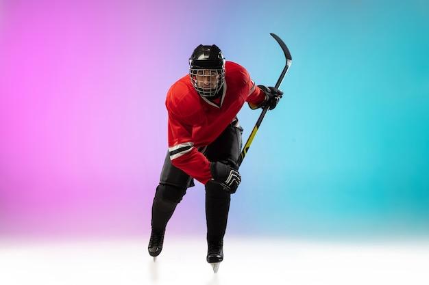 Jugador de hockey masculino con el palo en la cancha de hielo
