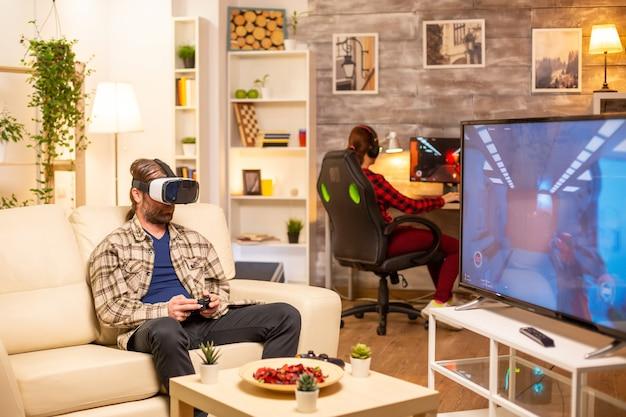 Jugador de hombre usando un auricular vr para jugar videojuegos en la sala de estar a altas horas de la noche