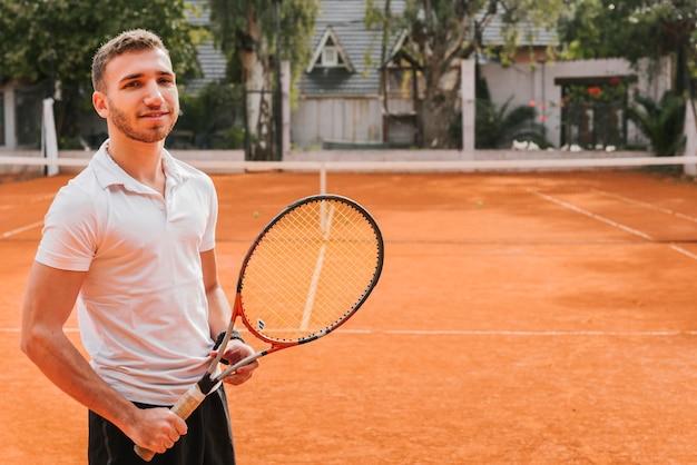 Jugador joven atlético de tenis posando