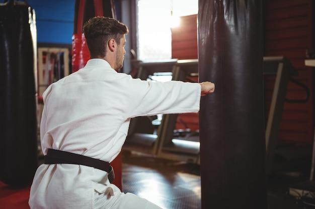 Jugador de karate golpeando una bolsa de boxeo
