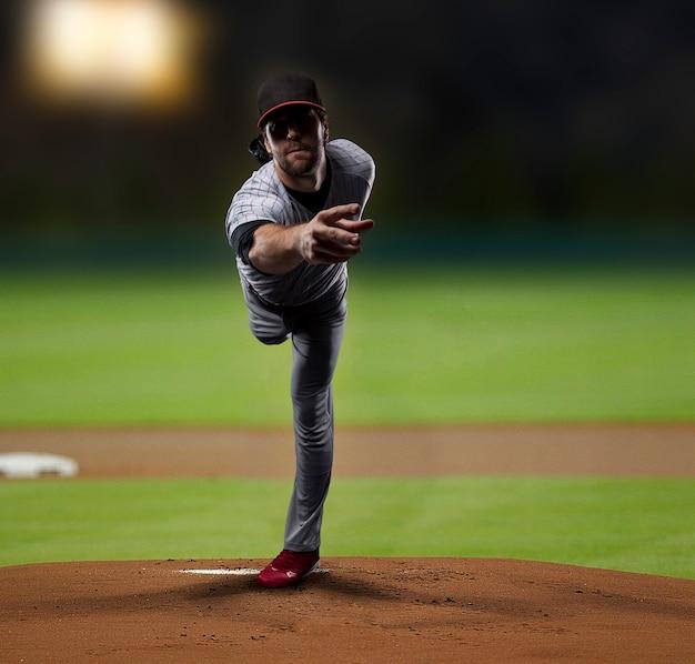 Jugador lanzador lanzando una pelota, en un estadio de béisbol.