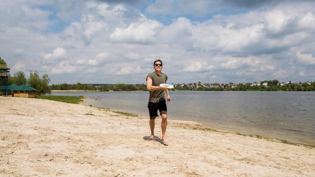 Jugador masculino del disco volador en la playa arenosa