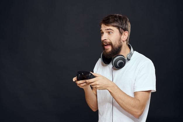 Jugador masculino jugando una consola con joysticks en auriculares