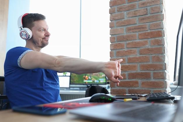 El jugador masculino se sienta en auriculares y mira molesto en el monitor. cómo jugar a alto nivel en línea