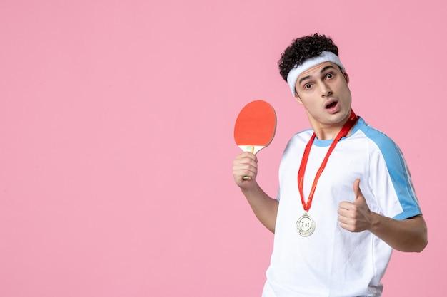 Jugador masculino de vista frontal con medalla sosteniendo raqueta pequeña