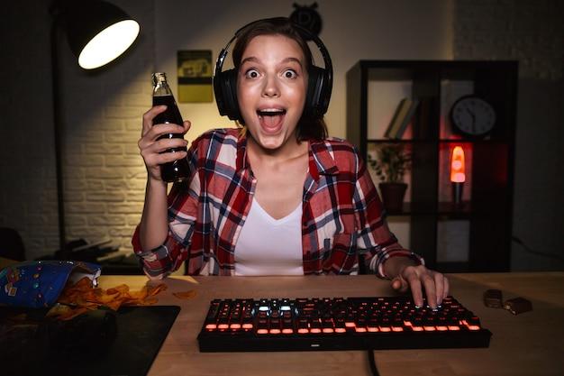 Jugador de mujer emocionada sentada en la mesa, jugando juegos en línea en una computadora en el interior, celebrando el éxito, bebiendo bebidas gaseosas
