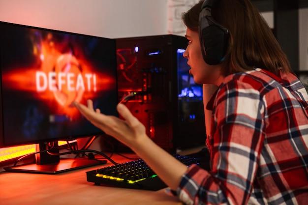 Jugador de mujer enojada sentado en la mesa, jugando juegos en línea en una computadora en el interior