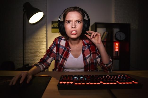 Jugador de mujer sorprendida sentada en la mesa, jugando juegos en línea en una computadora en el interior