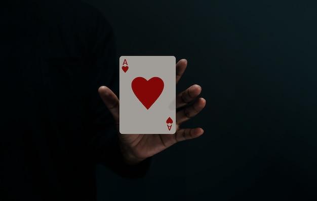 Jugador de naipes de ace heart o mago levitando una tarjeta de póquer en la mano metáfora de la felicidad del amor y comenzar una buena relación