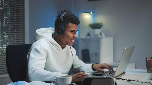 Jugador negro con capucha blanca y con auriculares jugando juegos en la computadora por la noche
