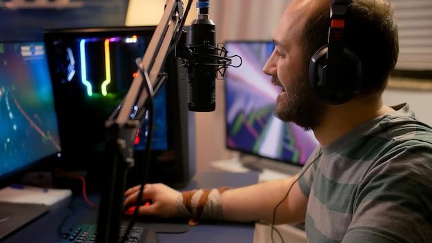 El jugador profesional pone auriculares profesionales y comienza a jugar con nuevos gráficos de videojuegos de disparos espaciales en una computadora potente