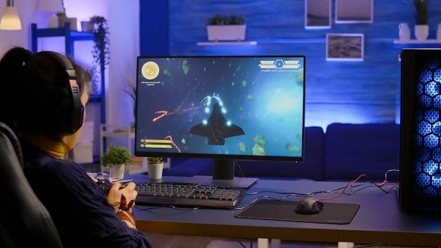 Jugador profesional que juega al campeonato en línea de disparos espaciales con gráficos modernos usando un controlador inalámbrico
