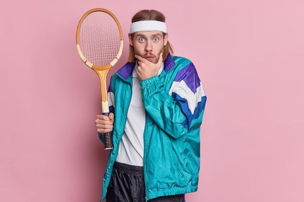 El jugador de tenis activo sorprendido sostiene la raqueta y mira asombrado sostiene la barbilla tiene cerdas gruesas, usa diadema y ropa deportiva.