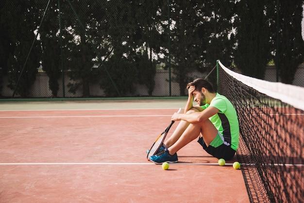 Jugador de tenis apoyado contra red en frustración