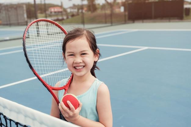 Jugador de tenis asiático joven de la muchacha en corte azul al aire libre
