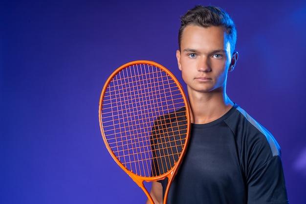Jugador de tenis caucásico joven posando con raqueta de tenis
