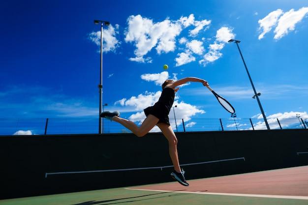 Jugador de tenis de chica sexy con raqueta de tenis en la cancha. joven mujer está jugando tenis.
