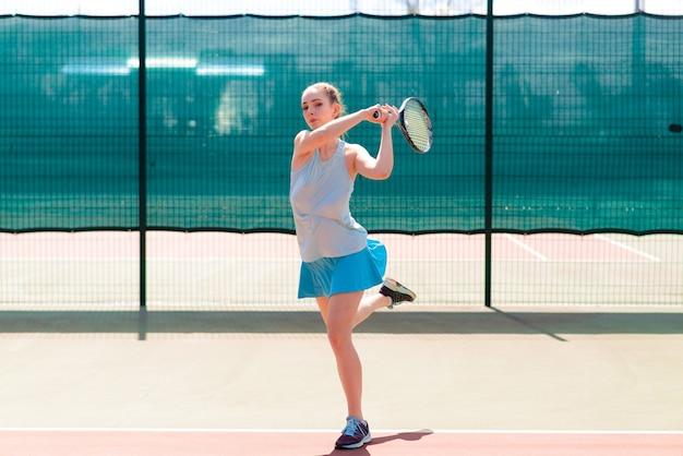 Jugador de tenis chica sexy en vestido blanco y tacones con raqueta de tenis