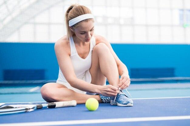Jugador de tenis femenino atar zapatos