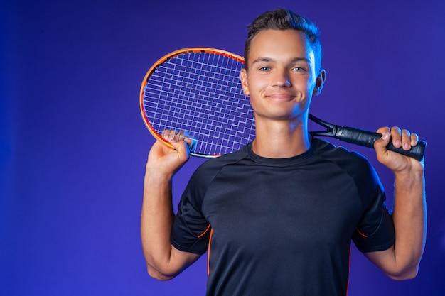 Jugador de tenis joven caucásico posando con raqueta de tenis sobre fondo púrpura cerrar