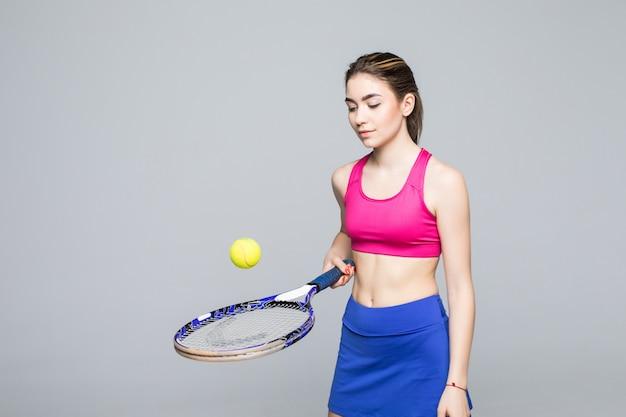 Un jugador de tenis de la mujer que despide la bola en la raqueta, aislada.