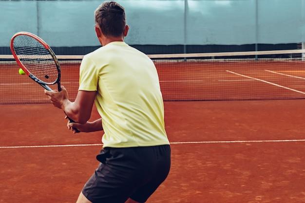 Jugador de tenis de pie con raqueta en la cancha de tenis al aire libre