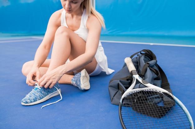 Jugador de tenis que ata los zapatos