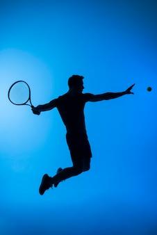 Jugador de tenis de tiro completo saltando