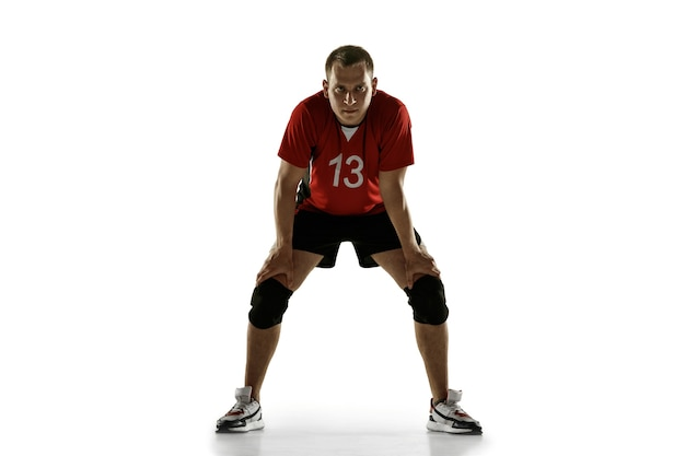 Jugador de voleibol caucásico joven placticing aislado sobre fondo blanco.