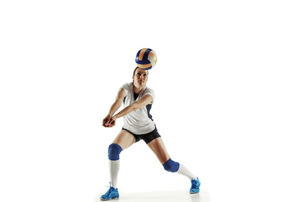 Jugador de voleibol femenino joven aislado en la pared blanca. mujer en equipamiento deportivo y zapatos o zapatillas de deporte entrenando y practicando. concepto de deporte, estilo de vida saludable, movimiento y movimiento.