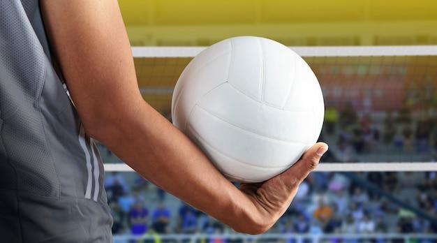 Jugador de voleibol con pelota en cancha de voleibol