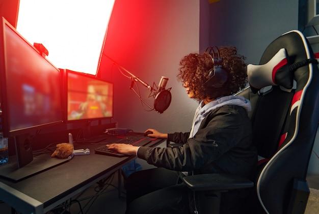 Jugadora profesional juega en videojuegos en su computadora. ella participa en torneos de juegos cibernéticos en línea, juega en casa o en un cibercafé. ella usa auriculares para juegos