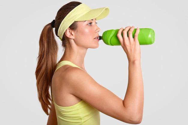 La jugadora de tenis bebe agua fría de la botella, toma un descanso después de un largo partido, vestida con gorra de tenis