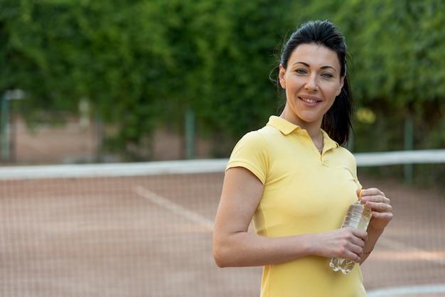 Jugadora de tenis con botella de agua