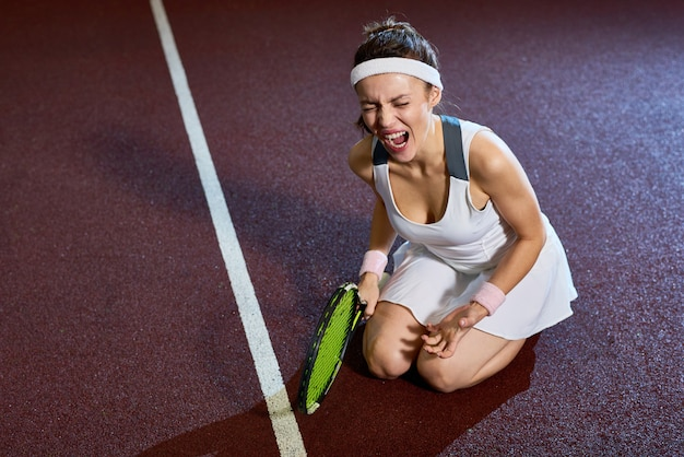 Jugadora de tenis lesionada en la práctica
