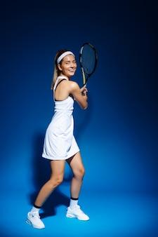 Jugadora de tenis con raqueta lista para golpear una pelota.