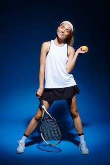 Jugadora de tenis con raqueta y pelota en la mano posando