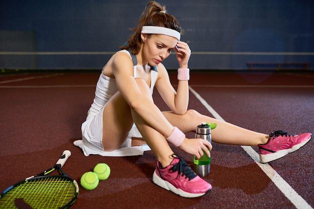 Jugadora de tenis sentada en la cancha