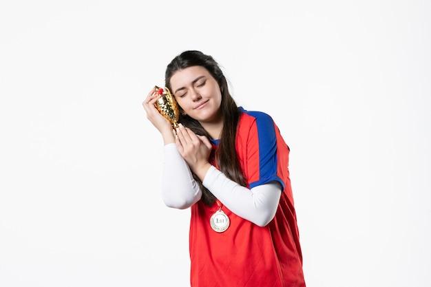 Jugadora de vista frontal con medalla y copa de oro