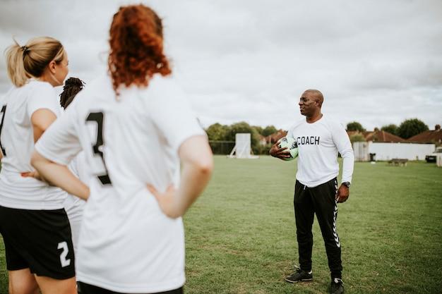 Jugadoras de fútbol femenino escuchando al entrenador.