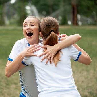 Jugadores de equipo feliz de tiro medio abrazándose