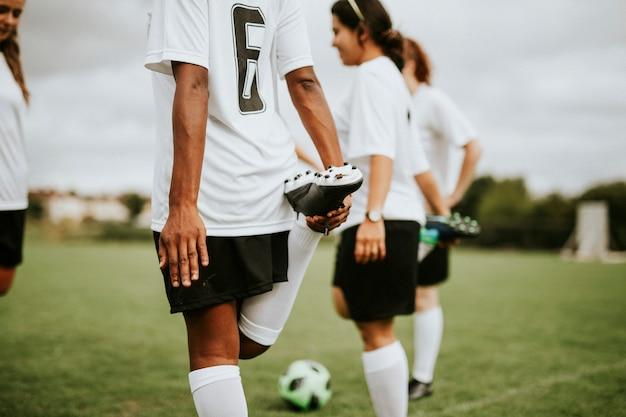 Jugadores del equipo de fútbol femenino estiramiento pre juego