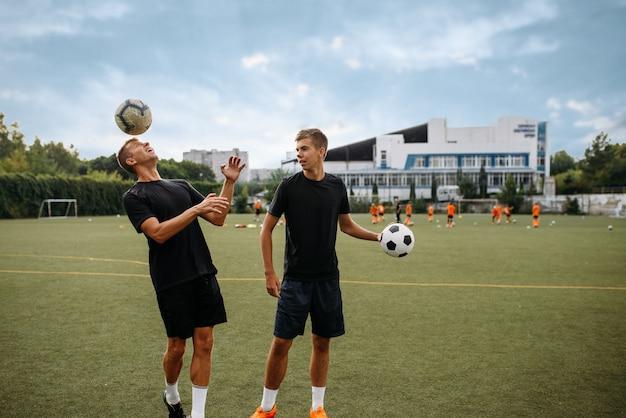 Jugadores de fútbol masculino entrenando con pelotas en el campo. futbolistas en el estadio al aire libre, entrenamiento del equipo antes del juego