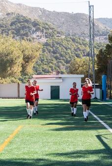 Jugadores de fútbol de tiro completo corriendo en el campo