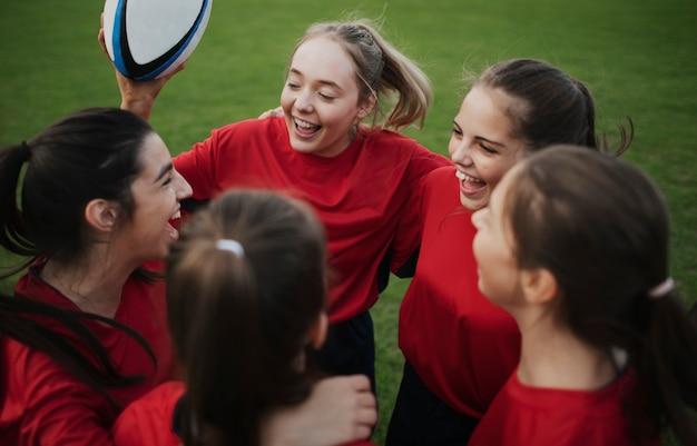 Jugadores de rugby jóvenes alegres en el campo