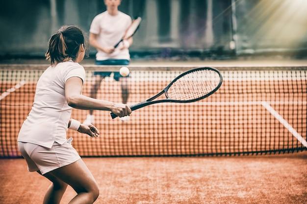 Jugadores de tenis jugando un partido en la cancha