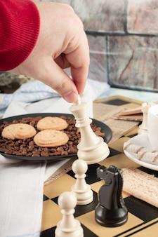 Jugando al ajedrez en una mesa de galletas de té